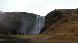 Skógafoss waterfall in the winter with tourism