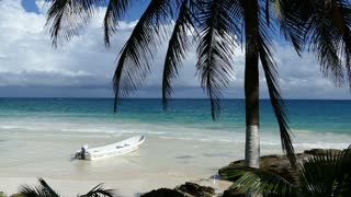 Small bay with a boat and palmtree at the coast in Tulum Yucatan, Mexico