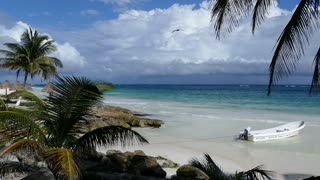Small bay with a boat and palmtrees at the coast in Tulum Yucatan, Mexico