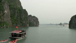 Small Cruise ship with canoes in Ha Long Bay