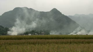 Smoke above farm land with mountains at the background in Mai Châu