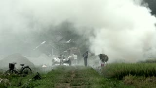 Smoke from burned hay and people working on farm land in Mai Châu