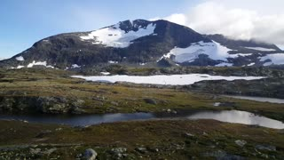Snowy mountains and a lake in Jotunheimen National Park Norway