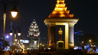 Statue of King Father Norodom Sihanouk with the Independence Monument at the background at night in Phnom Penh Cambodia