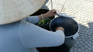 Stirring in a pan with Xi Ma black sesame sweet soup on the street of Hoi An Vietnam