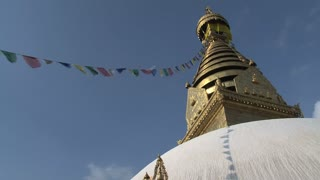 Swayambhunath stupa, monkey temple with prayer flags in the wind with a shadow on the stupa