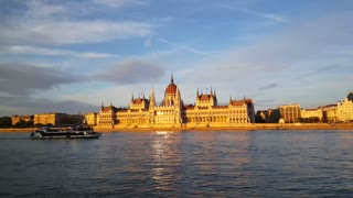 The Hungarian Parliament Building (Parliament of Budapest) in the evening light with a cruise ship passing by