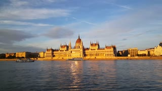 The Hungarian Parliament Building (Parliament of Budapest) in the evening light with a cruise ships passing by