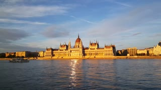 The Hungarian Parliament Building (Parliament of Budapest) in the evening light with a small cruise ship passing by