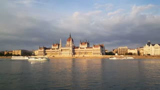 The Hungarian Parliament Building (Parliament of Budapest) in the evening with cruise ships passing by