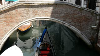 Tilt from Gondola in a canal to a bridge in Venice Italy