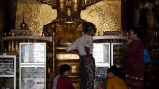 Tilt from people to a big buddha in the Ananda Temple in Bagan, Myanmar, Burma