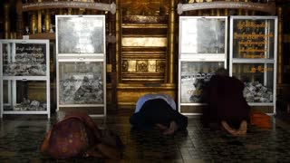 Tilt from people worship and pray to a big buddha in the Ananda Temple in Bagan, Myanmar, Burma