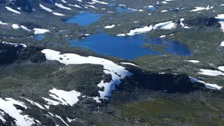 Tilt up from a lake to a mountain landscape in Jotunheimen National Park Norway
