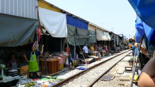 Time lapse from the train passing by at the Maeklong Railway Market (Talad Rom Hoop) in Samut Songkhram, Thailand