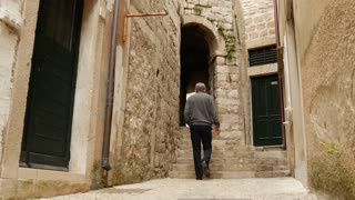 Tourist man walking through an alley in the streets of Dubrovnik Croatia