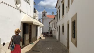 Tourist walking in the old town of Lagos Algarve Portugal