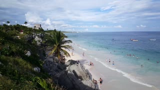 Tourists at the beach in front of the ancient Mayan fortress in Tulum Yucatan, Mexico