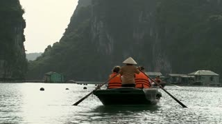 Tourists in a boat sailing through a fishing village in Ha Long Bay