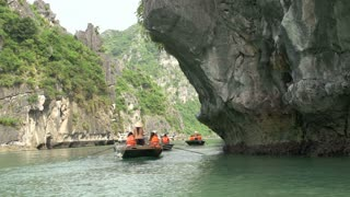 Tourists in a boat trip close by the high mountains and rocks in Ha Long Bay