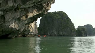 Tourists in a boat trip close to the high mountains and rocks in Ha Long Bay