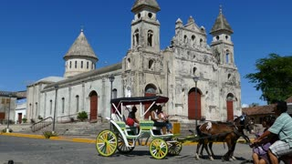 Tourists in a horse and carriage passing by the Guadalupe Church in Granada Nicaragua