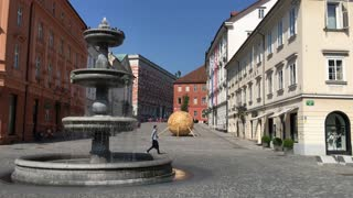Tourists passing by the fountain at the novi trg square in the old town of Ljubljana Slovenia