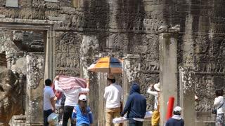 Tourists walking at the Bayon Khmer temple at Angkor Wat Cambodia