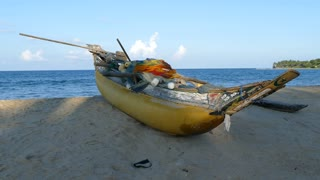 Traditional yellow catamaran fishing boat at the beach of Arugam Bay in Sri Lanka