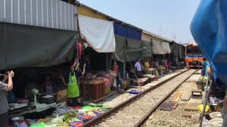 Train passing by at the Maeklong Railway Market (Taled Rom Hoop) in Samut Songkhram Thailand
