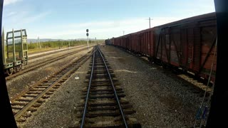 Trans-Siberian Railway train driving slowly when passing by a goods train and station