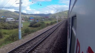 Trans-Siberian Railway train in a sharp curve between hills and a village