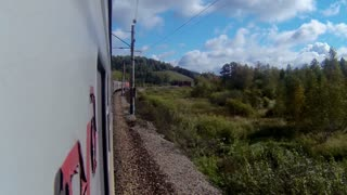 Trans-Siberian Railway train in a sharp curve between hills and forest