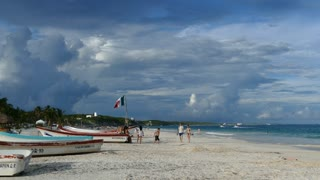 Tulum beach with boats and the Mexican flag