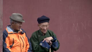 two elderly man sitting on a bench at the Gandan Monastery in Ulaan Bataar, Mongolia