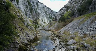 Flying through a gorge above a river at Picos de Europa in Spain