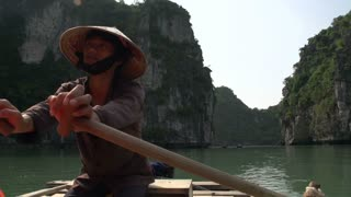 Vietnamese guy rowing the boat with tourist with a pan to the mountains