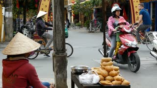 Vietnamese lady selling bread at a crossroad in the old town of Hoi An Vietnam