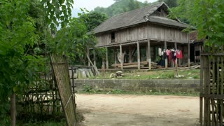 Volunteer farmers passing by a stilts house with hay in Mai Châu