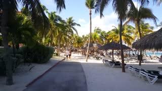 Walking at Palm Beach on Aruba passing by tourists