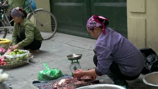 Woman cutting fish in the streets of Hanoi, Vietnam