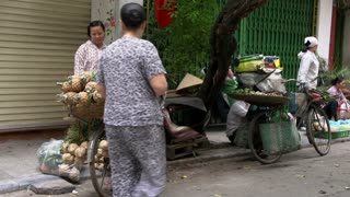 Woman walks to a girl who is selling pineapple from her bike in the streets of Hanoi, Vietnam