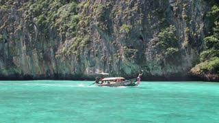 Wooden boat arrives at the beach at Phi Phi island