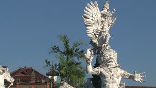 Zoom out from Statue to traffic in Bali