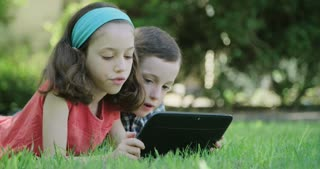 A girl and her brother laying on the grass holding a tablet computer