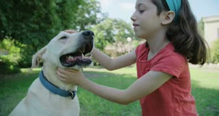 A girl playing with her big white dog