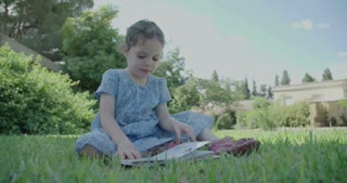 A little girl reading a children's book sitting outdoors on the grass