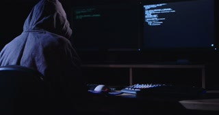 Anonymous hacker sitting in a dark room in front of screens and hacking computer systems