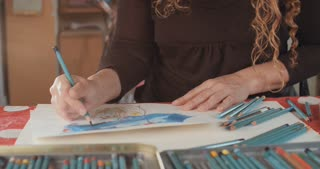 artist drawing with colored pencils in her studio