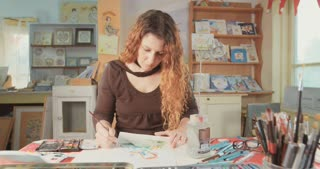 Artist painting with water colors in her studio